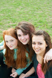 Three different girls are sitting on the grass and Royalty Free Stock Image