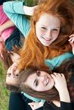 Three different girls are sitting on the grass and Stock Photos