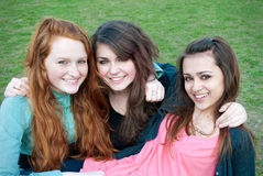 Three different girls are sitting on the grass and Royalty Free Stock Photography