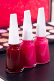 Three different nail polish colors and a make up background - red, pink and light pink Stock Photography