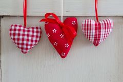 Three different red ornamental hearts hanging. Royalty Free Stock Photography