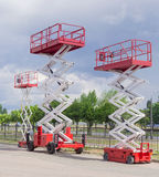 Three different scissor wheeled lifts on asphalt ground Stock Photography