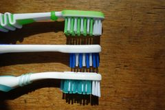3 different tooth brush heads on wood. Three different tooth brush heads on wood Royalty Free Stock Photos