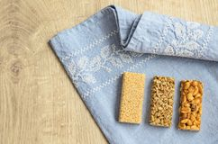 Three different types of gozinaki bars with sunflower seeds, peanuts and sesame seeds on a blue tablecloth background with embroid. Ery on a wooden background Stock Photo