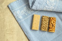Three different types of gozinaki bars with sunflower seeds, peanuts and sesame seeds on a blue tablecloth background with embroid. Ery on a wooden background Royalty Free Stock Photos