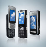 Three different types of mobile phones. Three mobile phones, different types on gray background Stock Images