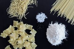 Three different types of pasta are laid out on black background royalty free stock photography