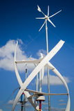 Wind energy. Three different types of windmill turbines generating wind power. A renewable energy source Royalty Free Stock Photos