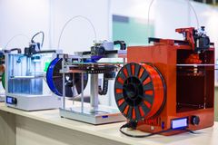 Three dimensional 3D printers during work at modern technology exhibition. Automatic 3D printers in row during work at modern technology exhibition. 3D printing stock photos