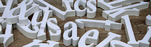 Three-dimensional letters of white letters intended for making advertisements are scattered on the floor. Three-dimensional letters of white letters intended for Royalty Free Stock Image