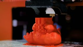 Three dimensional printing machine prints physical 3D model of red toy dragon. 3D printer prints physical 3D model of red toy dragon with plastic wire filament stock video footage