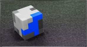 Three Dimensional White, Grey and Blue Cube Puzzle on a grey bac Royalty Free Stock Image