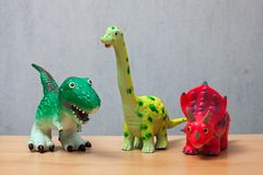 Three dinosaurs toys standing on a wooden floor.