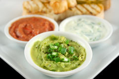 Three Dips. Comprising guacamole, capsicum and tzatzki dips with bread stock photography