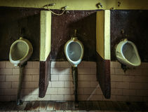 Three dirty urinals Stock Photos