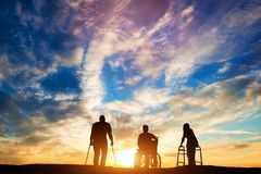 Three disabled people at the sunset. Stock Photo