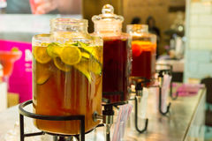 Three dispensers of ice tea with fruit slices Royalty Free Stock Images