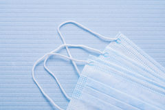 Three disposable face masks on blue background Stock Images