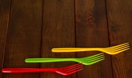 Three disposable plastic forks on wooden surface. Three disposable plastic forks on dark wooden surface Royalty Free Stock Images