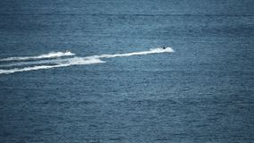 Three distant jet ski riders at sea, slow motion shot stock video
