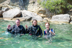Three Divers. Three happy scuba divers standing in shallow water before a dive.Two of them are wearing their scuba equipment Stock Image