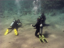 Three divers are training at the sea bottom. Three divers are sitting on the Red Sea bottom sand and training stock image