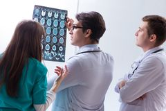 The three doctors discussing scan results of x-ray image. Three doctors discussing scan results of x-ray image Royalty Free Stock Images