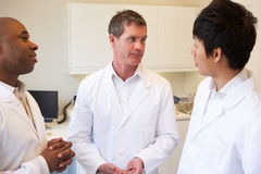 Three Doctors Having Discussion In American Hospital Royalty Free Stock Photos