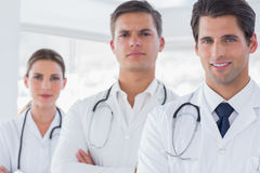 Three doctors with lab coats. Smiling to the camera royalty free stock photography