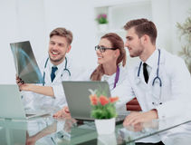 Three doctors looking attentively at x-ray and discussing it Royalty Free Stock Photography