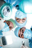 Three doctors in the operating cost of the patient. Doctor wearing surgical suits, masks and gloves. Royalty Free Stock Photos