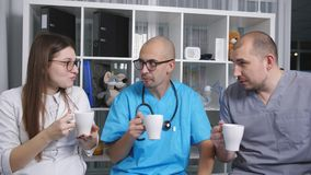 Doctors in the doctor`s lounge drinking coffee and talking on the break. stock footage
