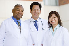 Three Doctors Standing Outside A Hospital Stock Image