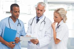 Three doctors using a tablet Stock Image