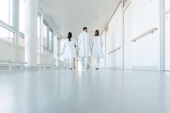 Three doctors walking down a corridor in hospital