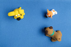 Three dogs from plasticine on a blue background Royalty Free Stock Photo