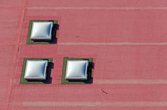 Three domed roof-lights on a red flat roof Stock Photography
