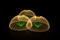 Three domes made of light. Three green swirls, captured in three domes of light on a black asphalt road Royalty Free Stock Image