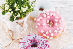 Three donut, a cup of coffee and flowers on a white table Royalty Free Stock Image