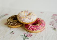 Three donuts on a background in the style of a shabby chic. Wooden light background with flowers. Decoupage technique. Donuts are pink, white, and chocolate stock image
