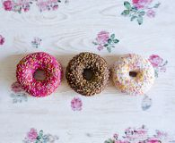 Three donuts on a background in the style of a shabby chic. Wooden light background with flowers. Decoupage technique. Donuts are pink, white, and chocolate royalty free stock photography