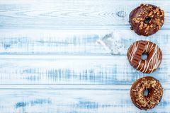 Three donuts with chocolate glaze on an old wood background. Space for text. Top view stock image