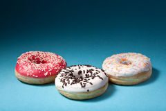 Three donuts with color icing isolated on blue background Stock Photography