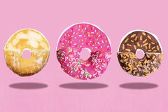 Three donuts, Cream, chocolate and pink glazed are cut and drawn fly in air royalty free stock photography