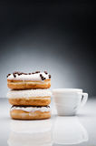 Three donuts and cup of coffee on dark background Royalty Free Stock Photo