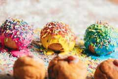 Three donuts laying on a messy kitchen counter. Three decorated doughnuts laying on a messy kitchen counter. Homemade bakings Stock Images