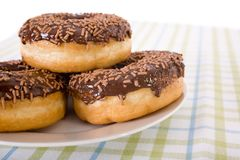 Three donuts on a plate, chocolate glazing Royalty Free Stock Image