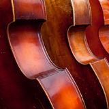 Three double basses in a row. Closeup of three double basses in a row stock images