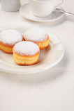 Three doughnuts on white plate Stock Images