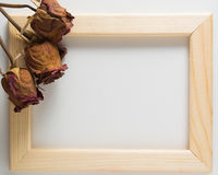 Three dried red roses with wooden frame Royalty Free Stock Photo